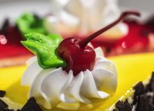 Un pedazo de torta con crema y la cereza Fotografía de archivo libre de regalías