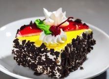 Un pedazo de torta con crema y la cereza Foto de archivo