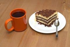 Un pedazo de torta de esponja en una placa y una taza de primer del té Fotos de archivo libres de regalías