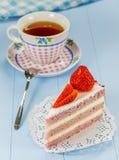 Un pedazo de torta de la fresa con una taza de té Fotos de archivo libres de regalías