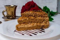 Un pedazo de torta, de taza blanca de té y de fresas Foco selectivo foto de archivo