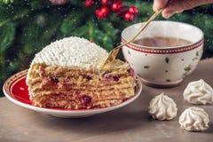 Un pedazo de torta del arándano cubierto con la crema blanca en la placa en el fondo del árbol de navidad Foto de archivo