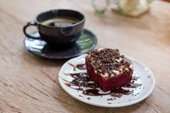 Un pedazo de torta roja del terciopelo con la taza de café en la tabla de madera Fotos de archivo