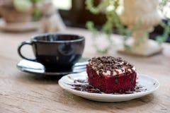Un pedazo de torta roja del terciopelo con la taza de café en la tabla de madera Fotografía de archivo