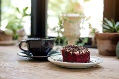 Un pedazo de torta roja del terciopelo con la taza de café en la tabla de madera Imagen de archivo libre de regalías