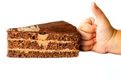 Un pedazo de torta y de una mano fotografía de archivo libre de regalías
