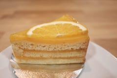 Un pedazo de una torta anaranjada en una placa blanca en la tabla dinning de madera imagen de archivo
