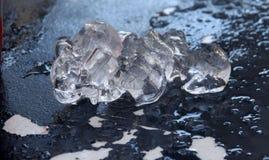 Un pedazo del hielo de fusión en la tabla de la peladura Imagen de archivo