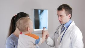 Un pediatra de sexo masculino joven prescribe y da píldoras El muchacho está en sus brazos del ` s de la madre Una mujer joven es almacen de video