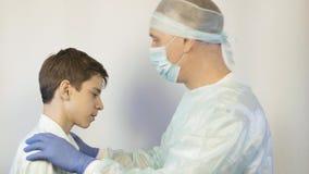 Un pediatra esamina ad un adolescente, chiede che cosa lo danneggia e gli dà una pillola archivi video
