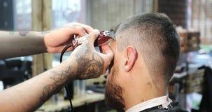 Un peluquero con los tatuajes en sus manos hace un modelo hermoso metrajes