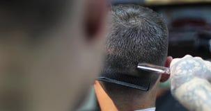 Un peluquero con los tatuajes en sus manos que cortan el pelo usando cepillo para el pelo y las tijeras almacen de video