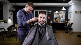 Un peluquero elegante habla con un visitante del salón de belleza que vino conseguir uqdaku y restaure un corte de pelo en barber almacen de video