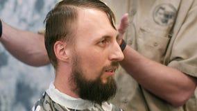 Un peluquero está cortando a un hombre con una barba almacen de video
