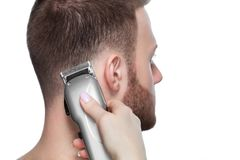 Un peluquero hace un corte de pelo para un hombre joven en una barbería Fotografía de archivo libre de regalías