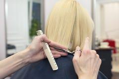 Un peluquero que hace el corte de pelo para un cliente femenino rubio Foto de archivo libre de regalías