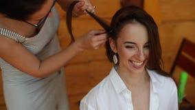 Un peluquero que hace el pelo de una morenita hermosa Un primer La mañana del ` s de la novia almacen de metraje de vídeo