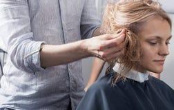 Un peluquero que hace un corte de pelo para un cliente femenino rubio Fotos de archivo