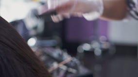 Un peluquero que peina a la muchacha del pelo almacen de metraje de vídeo