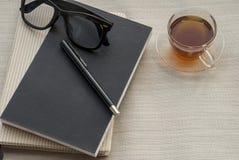 Un penna, taccuino, vetri e tè di vetro fotografie stock libere da diritti