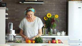 Un pensionista moderno está preparando una ensalada en casa en la cocina Ella concentra los tomates Su pelo se ata con a almacen de video