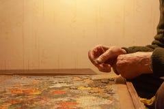 Un pensionista pone un rompecabezas en la tabla Él ama rompecabezas fotos de archivo libres de regalías