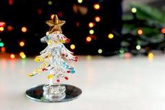 Un pequeño árbol de navidad del recuerdo hecho del vidrio en el fondo de las luces de la Navidad del centelleo, efecto del bokeh Imagen de archivo