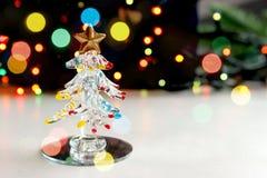 Un pequeño árbol de navidad del recuerdo hecho del vidrio en el fondo de las luces de la Navidad del centelleo, efecto del bokeh Fotos de archivo libres de regalías