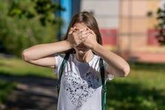 Un pequeño adolescente la cubrió los ojos con sus manos En el verano en el aire abierto Un día asoleado brillante r Fotos de archivo