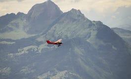 Un pequeño aeroplano rojo que vuela sobre las montañas Fotos de archivo