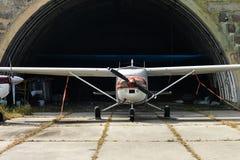 Un pequeño avión biplaza está en un hangar en el aeropuerto fijado a la tierra Foto de archivo