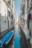 Un pequeño barco azul atado a una casa con una pared de ladrillo en un canal estrecho, Venecia, Italia Imagen de archivo libre de regalías