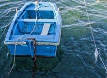 Un pequeño barco azul que flota en el mar Imagenes de archivo