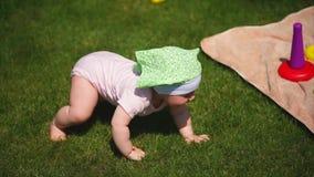 Un pequeño bebé en resbaladores se arrastra a lo largo de la hierba verde en un día de verano metrajes