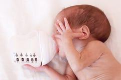 Un pequeño bebé prematuro que come una fórmula de la leche de una botella imagenes de archivo