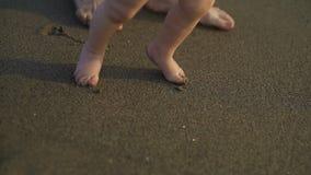 Un pequeño bebé que camina descalzo en la arena La madre enseña al niño a caminar metrajes