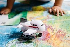 Un pequeño bebé que juega con un juguete de los aviones en el mapa del mundo, manos de los childs, viaje con los niños imagen de archivo