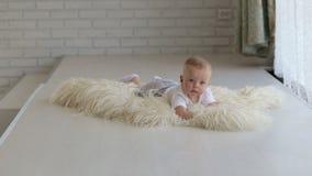 Un pequeño bebé recién nacido que miente en una manta mullida en casa en la cama en un cuarto almacen de video