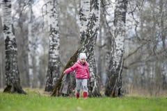 Un pequeño bebé rizado en una diversión rosada de la chaqueta y de las botas corre en el bosque de la primavera que la primera fl imágenes de archivo libres de regalías