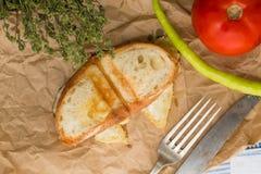 Un pequeño bocadillo con queso, un tomate y una pimienta fresca verde Imagen de archivo libre de regalías