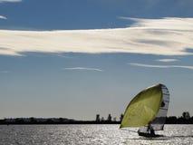 Un pequeño bote con la vela amarilla grande bajo navegación del cielo azul en un lago Fotos de archivo