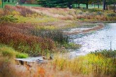 Un pequeño bote de remos que se sienta en el lado del lago en Morton Arboretum en caída foto de archivo