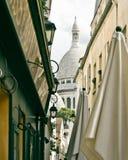 Un pequeño callejón en Montmartre con la iglesia de Sacre Coeur en vagos Imágenes de archivo libres de regalías