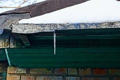 Un pequeño carámbano en un tejado verde debajo de la nieve fotografía de archivo