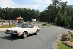 Un pequeño coche de deportes italiano clásico ascendente más cercano en el camino en declive Imagen de archivo