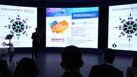 Un pequeño grupo de personas de nacionalidad asiática está mirando la pantalla grande en el pasillo durante la conferencia HD almacen de metraje de vídeo