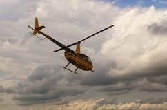 Un pequeño helicóptero privado amarillo vuela en dirección de las nubes tormentosas Un pequeño campo de aviación privado en Zhyto foto de archivo