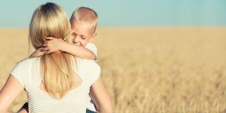 Un pequeño hijo abraza suavemente a su madre en un campo de trigo fotos de archivo libres de regalías