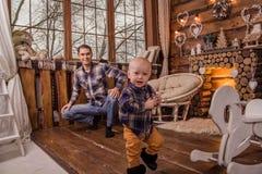 Un pequeño hijo corre alrededor del cuarto de madera con una chimenea Imagen de archivo