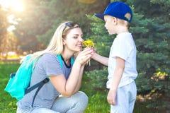 Un pequeño hijo da a su madre querida un ramo de dientes de león imágenes de archivo libres de regalías